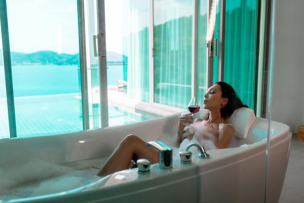 Morena linda nua encontra-se em um banho de espuma com um copo de vinho tinto pela janela aberta