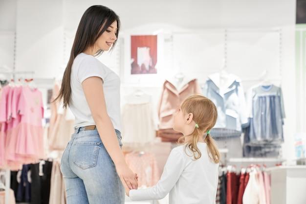Morena mãe e menina na loja com roupas de crianças.