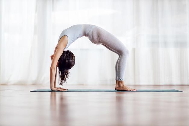 Morena magra e flexível com cabelo comprido na posição de ioga de roda. interior do estúdio de ioga.