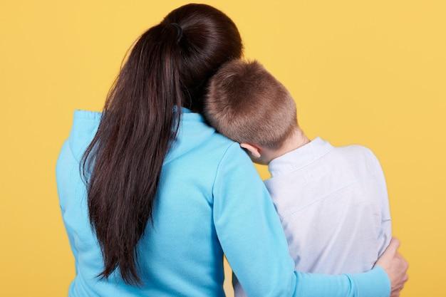 Morena menino e mãe sentados juntos, abraços, amor, família.