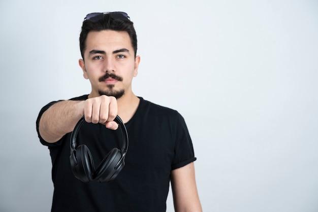 Morena modelo homem em pé e segurando fones de ouvido contra uma parede branca.