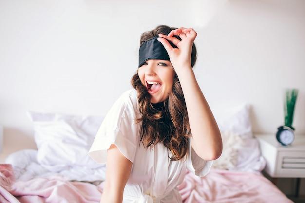 Morena morena bonita jovem acorda em sua cama. mulher atraente positiva posando na câmera e sorriso. segure a mão na máscara de dormir. sozinho no quarto. pijama rosa.