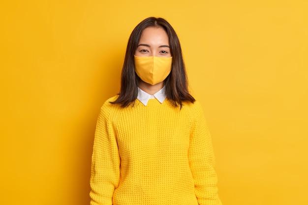 Morena muito jovem asiática usa máscara protetora se protege contra a pandemia de coronavírus, vestida com um macacão casual.