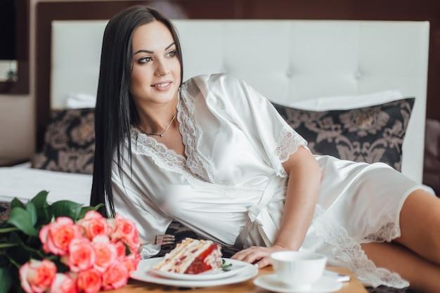 Morena muito linda garota deitada na cama pela manhã no quarto dela, perto de uma bandeja com um pedaço de bolo com café e um buquê de rosas.