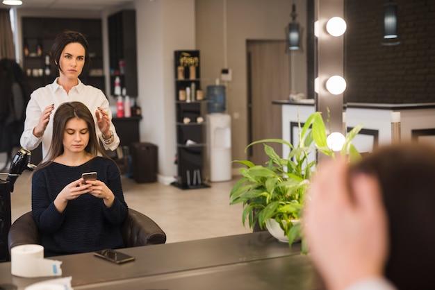 Morena, mulher, com, telefone móvel, obtendo, dela, cabelo