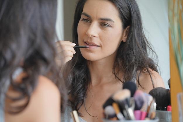 Morena, mulher, frente, espelho, aplicando, lipstik