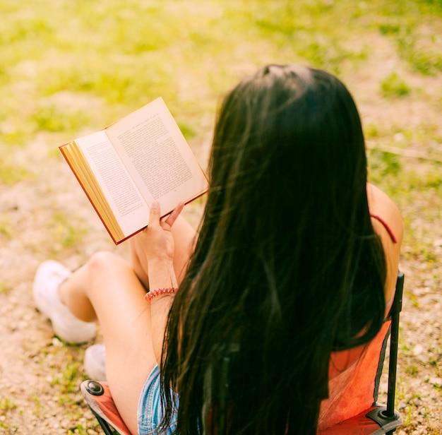 Morena mulher lendo livro na natureza