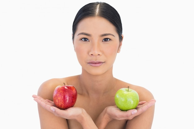 Morena natural segurando maçãs em ambas as mãos