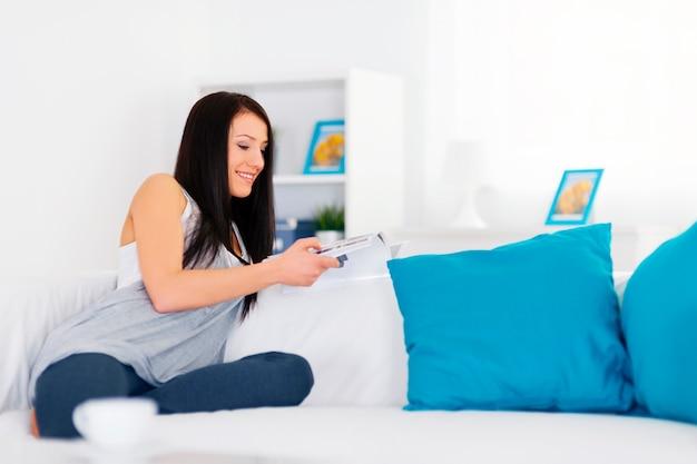 Morena no sofá lendo revista