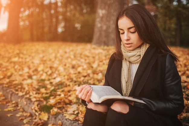 Morena nova bonita que senta-se nas folhas de outono caídas em um parque, lendo um livro.