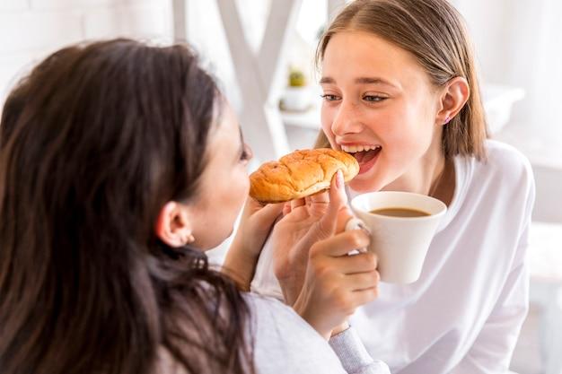 Morena oferecendo uma mordida de croissant para namorada