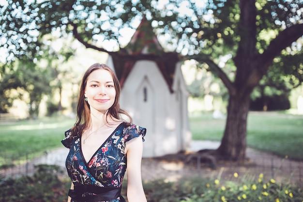 Morena otimista alegre em um vestido de flor no parque