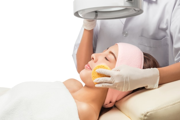 Morena pacífica recebendo micro dermoabrasão de terapeuta de beleza no spa de saúde.