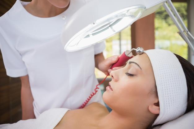 Morena pacífica recebendo micro dermoabrasão de terapeuta de beleza