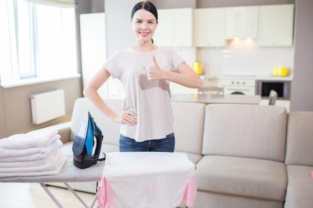 Morena positiva está posando na câmera. ela levanta o polegar grande e sorri. há uma roupa de ferro e branca na tábua de passar.