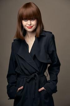 Morena romântica com fundo bege, pele clara, casaco preto