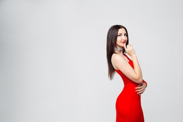 Morena sedutora em vestido vermelho brilhante