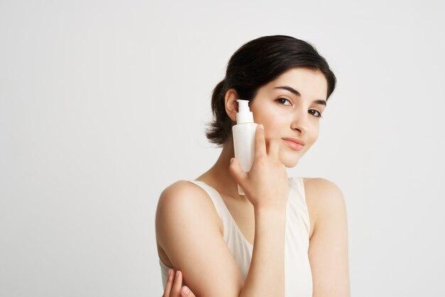 Morena segurando perto da pele limpa com loção facial