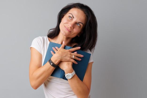 Morena, segurando um livro nas mãos dela, sobre um fundo cinza
