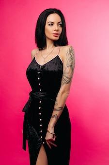 Morena sensual em elegante vestido preto sobre fundo cinza.