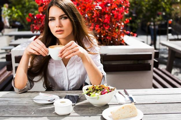 Morena sentada à mesa com café
