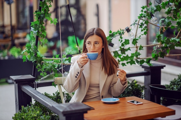 Morena sentada na cafeteria ao ar livre bebendo seu expresso