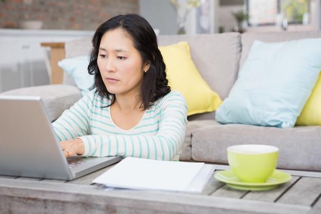 Morena séria usando laptop na sala de estar
