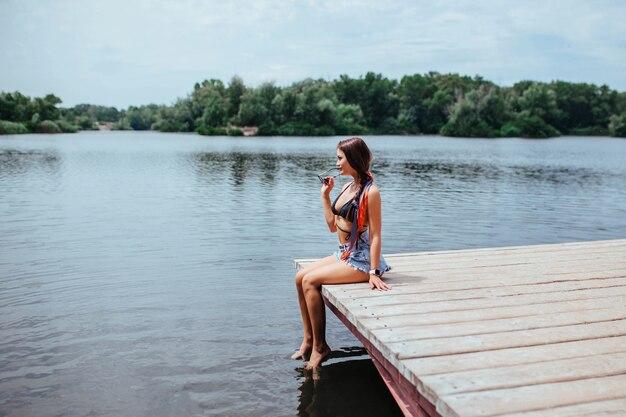 Morena sexy e linda se bronzear na ponte perto do lago ou rio em um maiô preto. conceito de turismo e lazer.