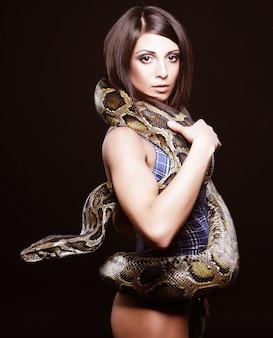 Morena sexy segurando python na parede preta