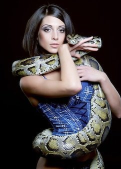 Morena sexy segurando python sobre preto