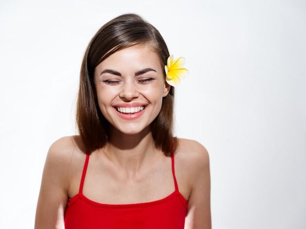Morena sexy sorrindo em um fundo claro e uma flor amarela no cabelo