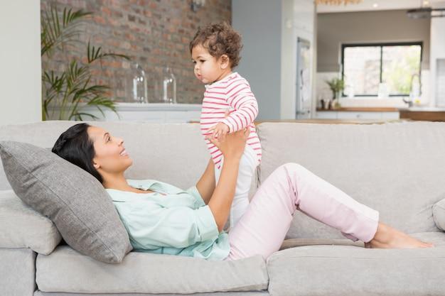 Morena sorridente brincando com seu bebê no sofá