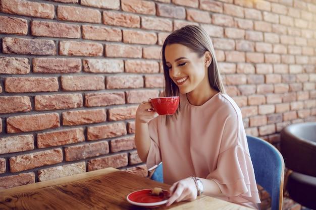 Morena sorridente com os olhos fechados vestido elegante desfrutando de café na cafeteria