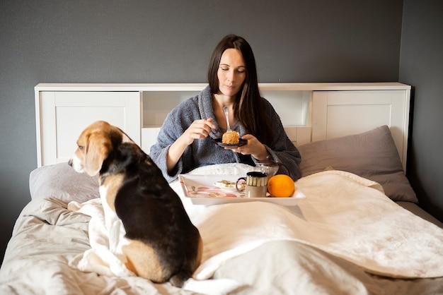 Morena sorridente comendo bolo de café da manhã e bebendo chá quente na cama em casa