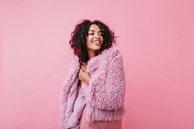 Morena sorridente e positiva com roupa rosa parece alegremente distante. retrato de menina com pele bronzeada.