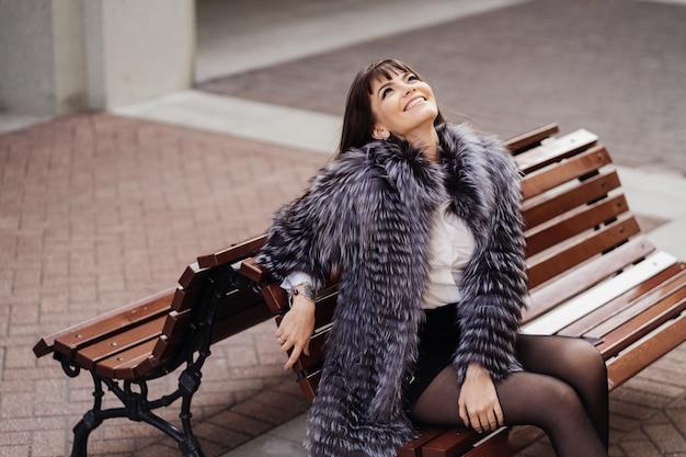Morena sorridente elegante com o cabelo longo e reto, vestindo um casaco de pele localização no banco e olhando para o céu