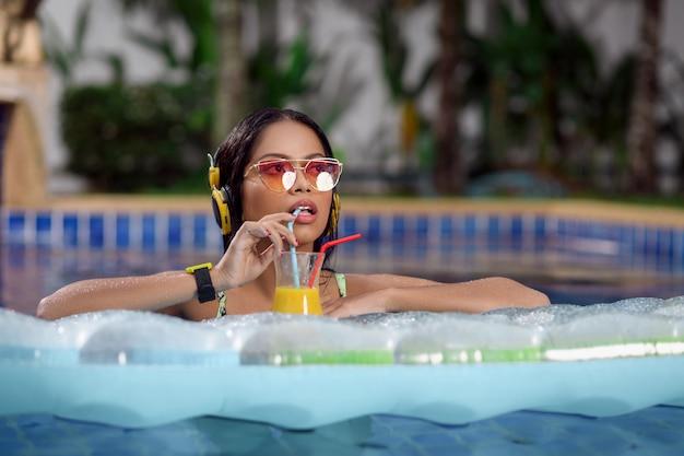 Morena sorridente interracial linda sexy posando na piscina com as mãos dobradas sobre um colchão de ar, em fones de ouvido amarelos e óculos de sol. com um coquetel na mão.