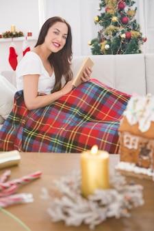 Morena sorridente lendo no sofá com capa