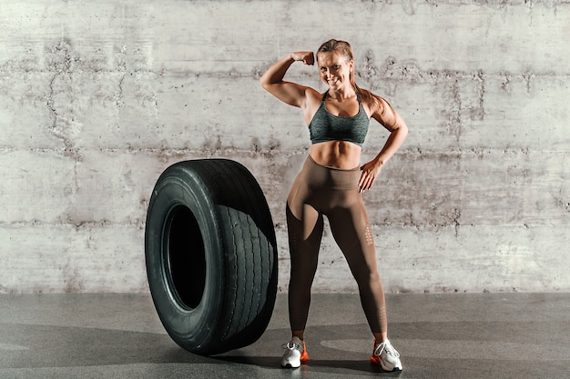 Morena sorridente muscular com rabo de cavalo e em roupas esportivas, posando ao lado de um grande pneu em frente a parede cinza no ginásio.