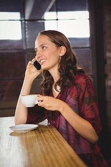 Morena sorridente tomando café e telefonando