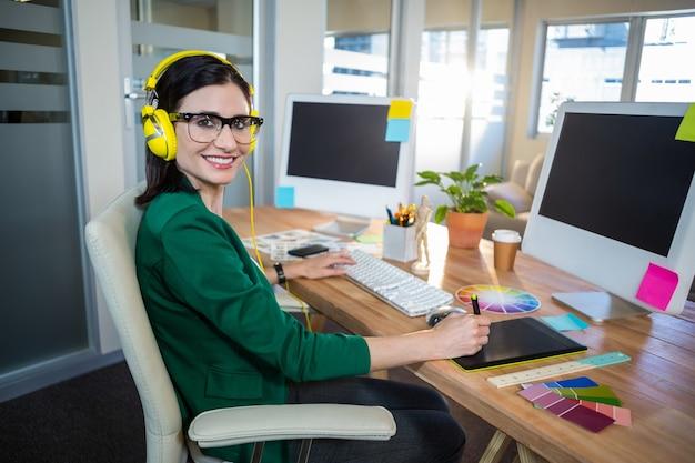 Morena sorridente trabalhando em sua mesa e ouvindo música