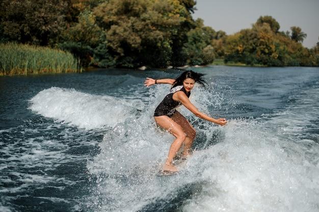 Morena surfgirl numa prancha de surf perto do mar