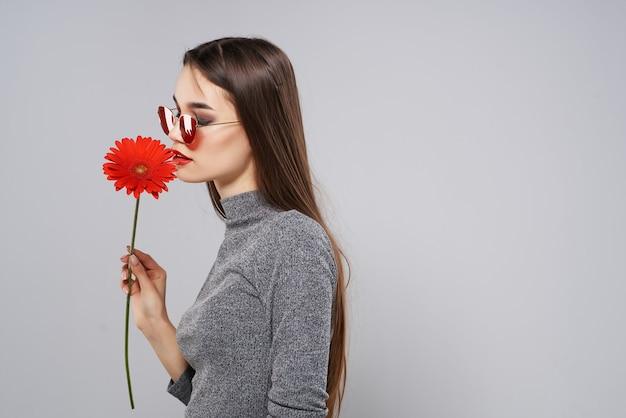 Morena usando óculos escuros, flor vermelha, paixão, estúdio de romance