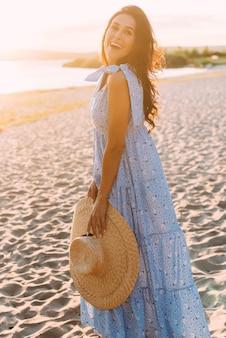 Morena woma em uma roupa de verão elegante e chapéu de palha sob os raios do sol na caminhada pela natureza