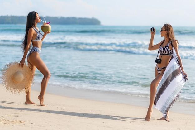 Morenas de luxo são representadas graficamente na praia. uma garota asiática bebe um coquetel de coco e uma garota européia atira nela com uma câmera retro.