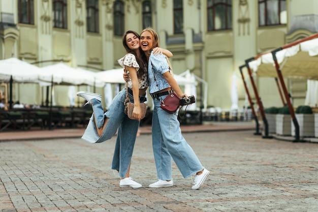 Morenas felizes bronzeadas e mulheres loiras de ótimo humor se abraçam lá fora