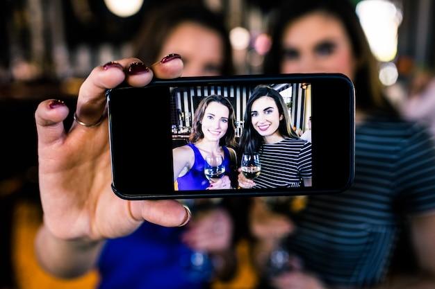 Morenas felizes tomando selfie com vinho branco em um bar