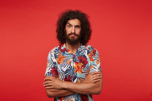 Moreno barbudo, bonito e confuso com cabelo encaracolado, mantendo as mãos cruzadas sobre o peito enquanto posa, olhando sério com sobrancelha levantada