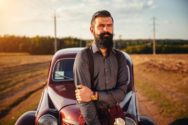 Moreno barbudo brutal com uma camisa, calças e suspensórios perto de um carro retrô marrom no fundo de uma estrada rural e o pôr do sol