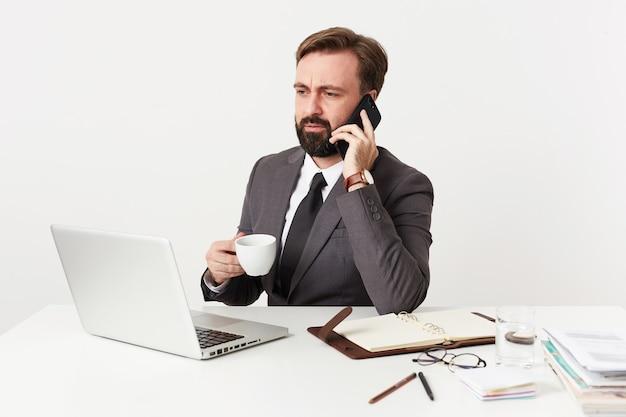 Moreno barbudo sério com roupas formais, segurando o copo branco na mão levantada enquanto conversa ao telefone, franzindo as sobrancelhas enquanto olha para a tela de seu laptop